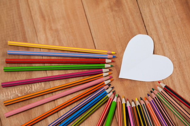 Kolorowy ołówek ułożony wokół papieru w kształcie serca