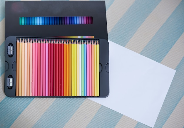 Kolorowy ołówek w pudełku na podłodze z makiety białego papieru