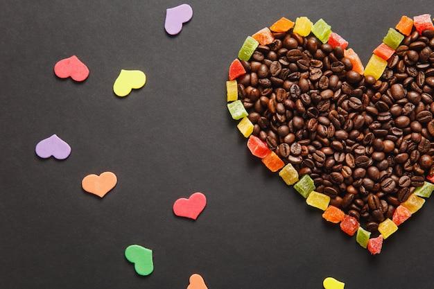 Kolorowy papier, kandyzowane owoce w formie serca, brązowe ziarna kawy na białym na czarnym tle do projektowania. karta świętego walentego, 14 lutego, koncepcja wakacje. skopiuj miejsce na reklamę.