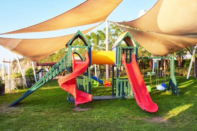 Kolorowy plac zabaw na podwórku w parku o zachodzie słońca.
