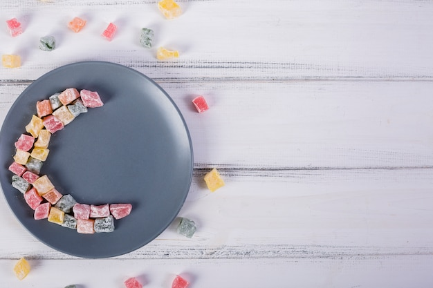Kolorowy półksiężyc wykonany z lukum na szarej płytce nad białym drewnianym stołem
