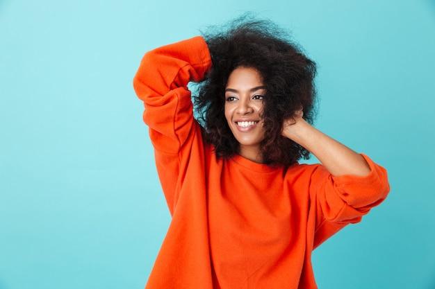 Kolorowy portret amerykańskiej kobiety w czerwonej koszuli, patrząc na bok z uśmiechem i dotykając jej potargane włosy, odizolowane na niebieskiej ścianie