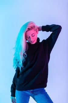 Kolorowy portret młodej pięknej dziewczyny o blond włosach w czarnej modnej bluzie z kapturem z niebieskimi dżinsami na neonowo różowym tle