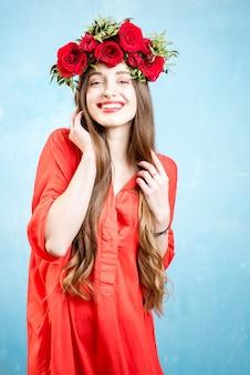Kolorowy portret pięknej kobiety w czerwonej sukience z wiankiem z czerwonych róż na niebieskim tle