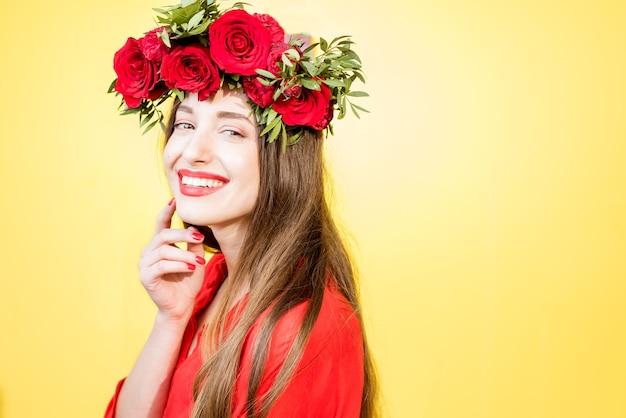 Kolorowy portret pięknej kobiety w czerwonej sukience z wiankiem z czerwonych róż na żółtym tle