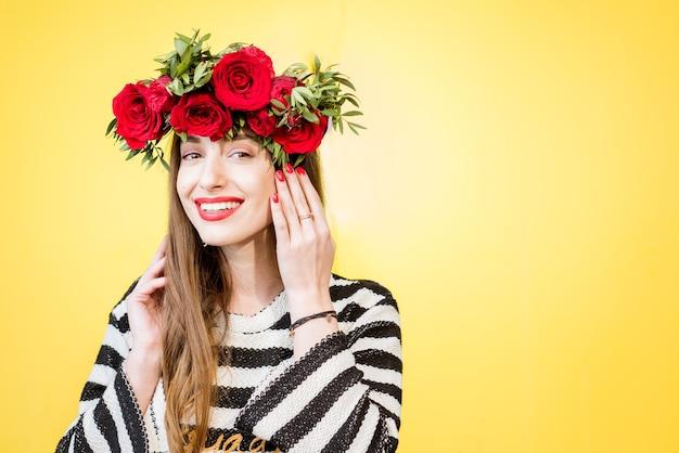 Kolorowy portret pięknej kobiety w swetrze z wiankiem z czerwonych róż na żółtym tle