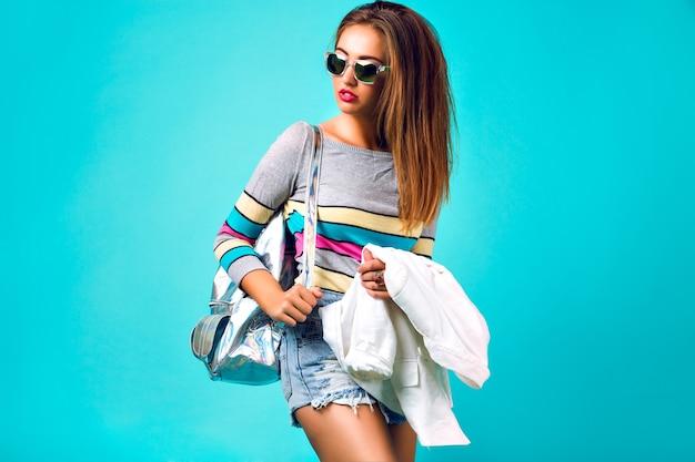 Kolorowy portret pięknej stylowej blondynki, jasny makijaż z puszystymi włosami, swobodny strój, okulary przeciwsłoneczne w plecaku, pastelowe wiosenne kolory. studio mody glamour.