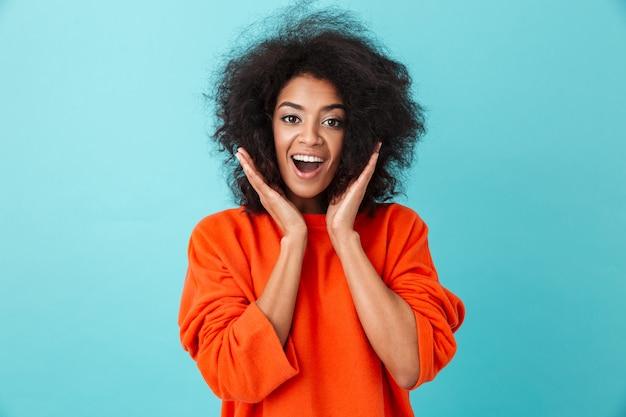 Kolorowy portret podekscytowanej kobiety w czerwonej koszuli, patrząc z uśmiechem i podnosząc ręce w twarz, na białym tle nad niebieską ścianą