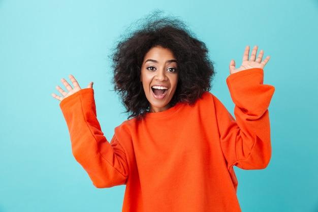Kolorowy portret szczęśliwej kobiety w czerwonej koszuli, patrząc z uśmiechem i podnosząc ręce w górę, na białym tle nad niebieską ścianą