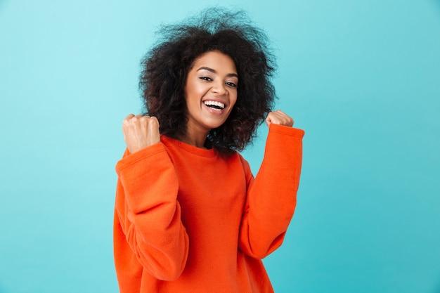Kolorowy portret szczęśliwej kobiety w czerwonej koszuli, patrząc z uśmiechem i zaciskającymi pięści jak zwycięzca, odizolowane na niebieskiej ścianie