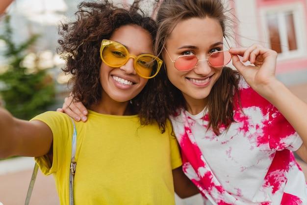 Kolorowy portret szczęśliwych przyjaciół młodych dziewcząt, uśmiechając się, siedząc na ulicy, biorąc zdjęcie selfie na telefon komórkowy, kobiety bawiące się razem
