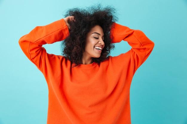 Kolorowy portret uśmiechnięta kobieta w czerwonej koszuli, patrząc na bok i dotykając jej ciemne kręcone włosy, odizolowane na niebieskiej ścianie