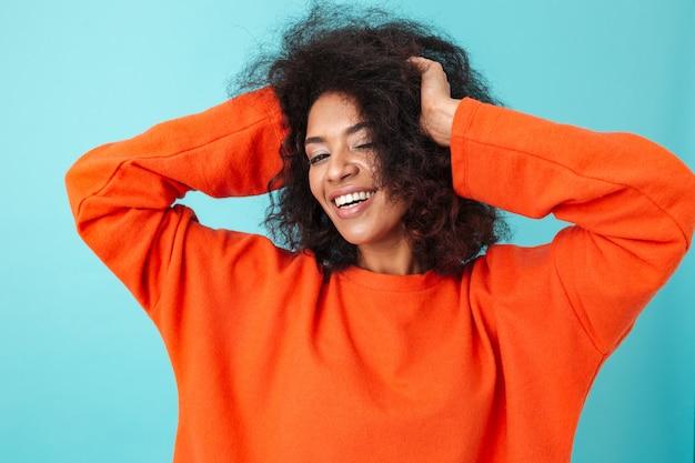 Kolorowy portret uśmiechnięta kobieta w czerwonej koszuli pozowanie i dotykając jej ciemne kręcone włosy, odizolowane na niebieskiej ścianie