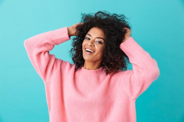 Kolorowy portret uśmiechnięta kobieta w różowej koszuli pozowanie i dotykając jej ciemną fryzurę afro, odizolowane na niebieskiej ścianie