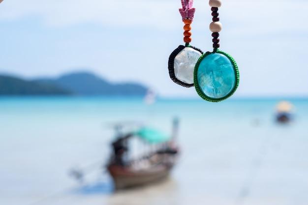 Kolorowy, ręcznie robiony brelok z kryształowych kamieni z niebieskim morskim tłem