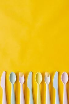 Kolorowy rozwidlenie, łyżka i nóż na żółtym tle z pustą przestrzenią dla teksta.