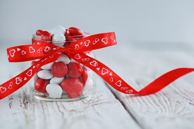 Kolorowy słoik ze słodyczami ozdobiony czerwoną kokardką z sercami.
