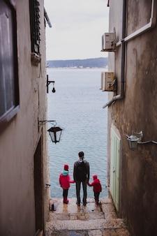 Kolorowy stary grodzki uliczny perspektywiczny widok w rovinj, istria, chorwacja. rodzina, ojciec i dwie córki patrzą na morze z ulicy
