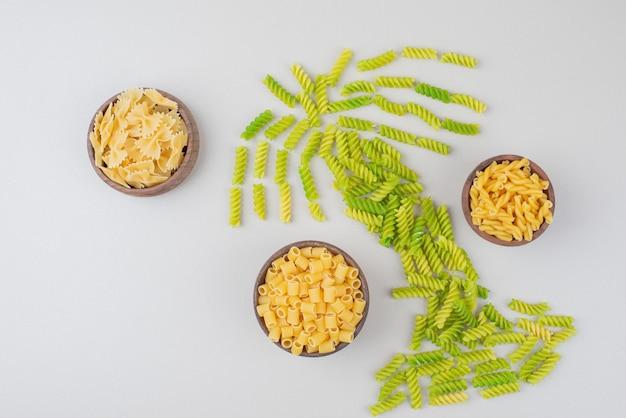 Kolorowy surowy makaron jako dłoń na białej powierzchni
