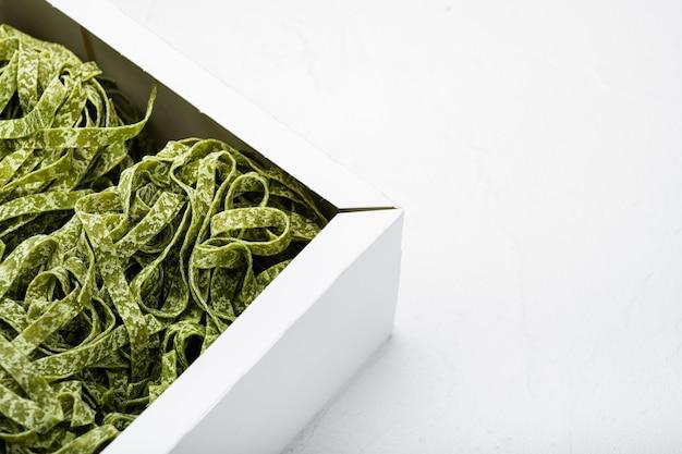 Kolorowy surowy włoski makaron tagliatelle w zestawie pudełkowym, na białym tle kamiennego stołu, z kopią miejsca na tekst