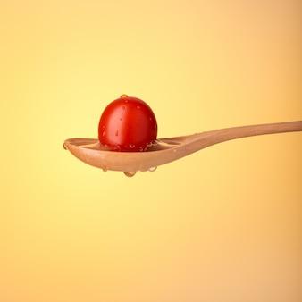 Kolorowy świeży czereśniowy pomidor na łyżce. ścieśniać