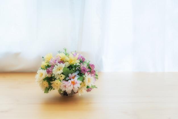 Kolorowy sztuczni kwiaty w ceramicznym garnku na drewno stole blisko okno z zasłoną.