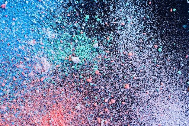 Kolorowy tło kredowy proszek. wielobarwne cząstki pyłu rozprysły się.