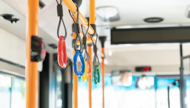 Kolorowy uchwyt dla pasażera stojącego w publicznym autobusie elektrycznym college'u, wnętrze pojazdu do transportu bezpieczeństwa