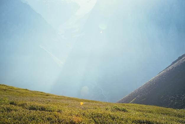 Kolorowy widok na gigantyczną ścianę górską ze strumieniem wody w słońcu. minimalistyczna słoneczna sceneria z promieniami słońca i rozbłyskiem słonecznym. minimalny widok alpejski. żywy krajobraz przyrody ze strumieniem na dużej górskiej ścianie