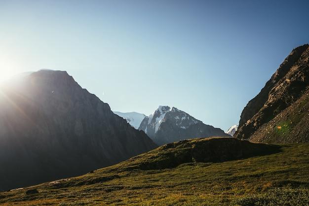 Kolorowy widok na wysoki ośnieżony szczyt górski i lodowiec w słońcu. piękna słoneczna sceneria z promieniami słońca i rozbłyskiem słonecznym. żywy krajobraz przyrody z dużym szczytem góry ze śniegiem. minimalny widok alpejski.