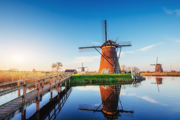 Kolorowy wiosenny dzień z tradycyjnym holenderskim wiatrakiem kanałem w rotterdamie. drewniane molo w pobliżu brzegu jeziora. holandia.