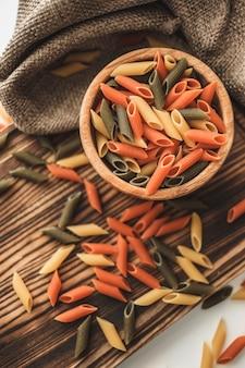 Kolorowy włoski makaron pszenny w drewnianej misce