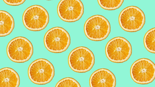 Kolorowy wzór owoców świeżych plasterków pomarańczy na nowoczesnym niebieskim tle. widok z góry