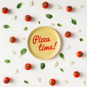 Kolorowy wzór składników pizzy wykonany z pomidorków koktajlowych, bazylii i sera na białej ścianie. koncepcja gotowania.