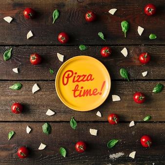 Kolorowy wzór składników pizzy wykonany z pomidorków koktajlowych, bazylii i sera na drewnianej ścianie. koncepcja gotowania.