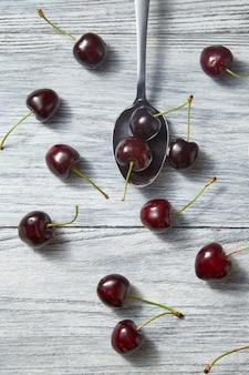 Kolorowy wzór z łyżką czerwonych soczystych wiśni z jagodami na szarym tle drewnianych. widok z góry