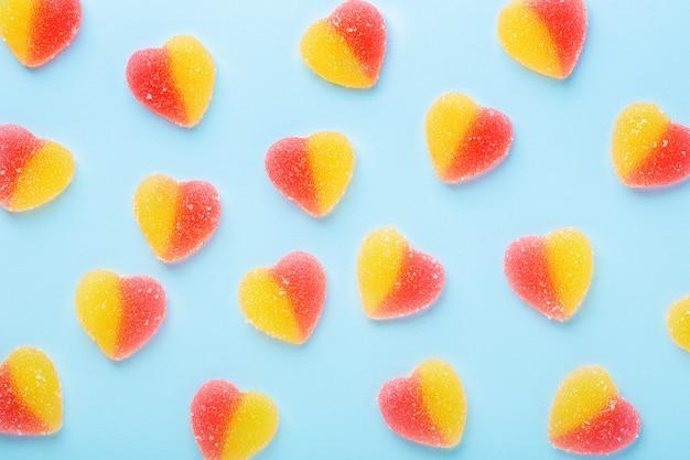 Kolorowy wzór żelki cukierki na niebieskim stole. galaretki w kształcie serduszka.