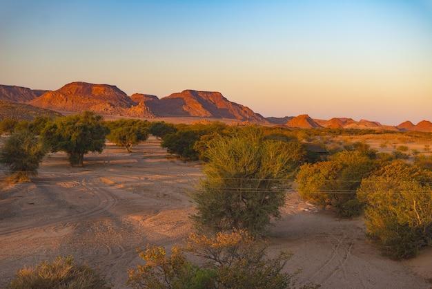 Kolorowy zachód słońca nad pustynią namib, namibia, afryka
