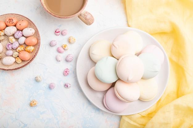 Kolorowy zefir lub ptasie mleczko z filiżanką kawy i drażetkami na białym betonie