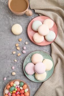 Kolorowy zefir lub ptasie mleczko z filiżanką kawy i drażetkami na szarym betonie