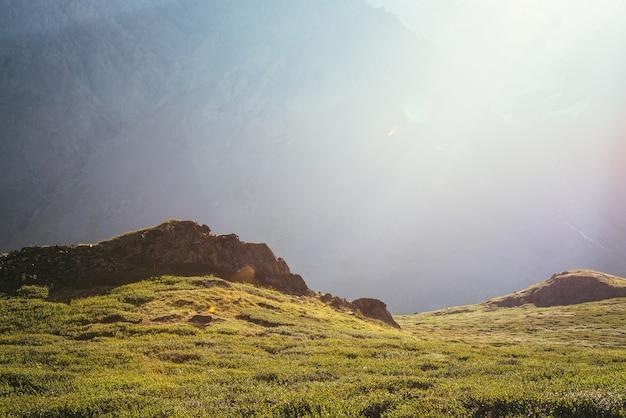 Kolorowy zielony krajobraz ze skałami i wzgórzami na tle gigantycznej ściany górskiej w słońcu. minimalistyczna żywa słoneczna sceneria z promieniami słońca i rozbłyskiem słonecznym. minimalny widok alpejski. malowniczy minimalizm.