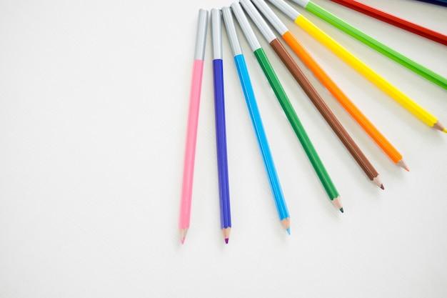 Kolory drewniane ołówka nakładają na drewniany stół biały.