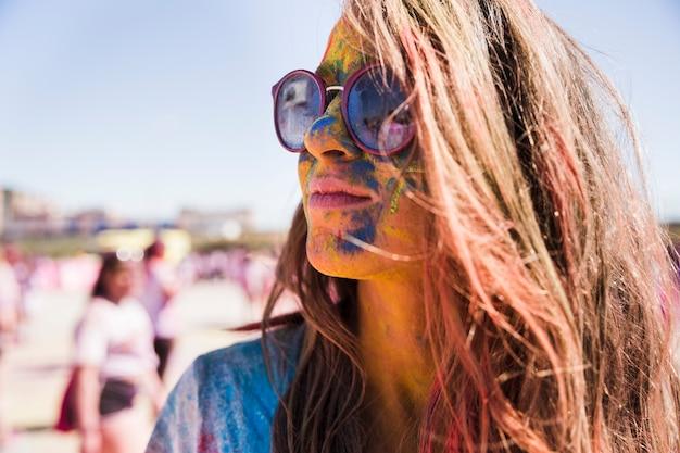 Kolory holi na twarzy kobiety w okularach przeciwsłonecznych