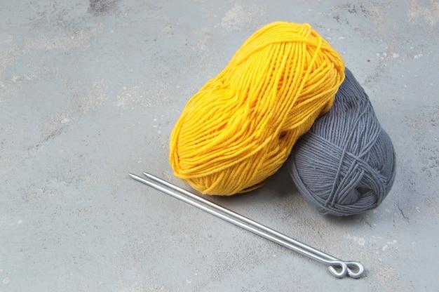 Kolory roku 2021. motki z żółtej i szarej włóczki wełnianej. nici do dziania i szydełkowania. kreatywność i hobby