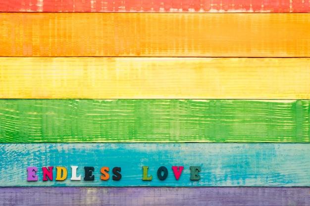 Kolory tęczy lgbt, drewniane tło, z napisem nieskończona miłość, lewy dolny róg, miejsce na kopię, układ płaski, widok z góry