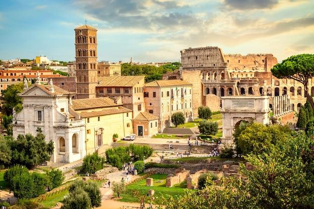 Koloseum i łuk konstantyna w rzymie, w słoneczny letni dzień słońca. światowej sławy punkt orientacyjny koloseum w rzymie.