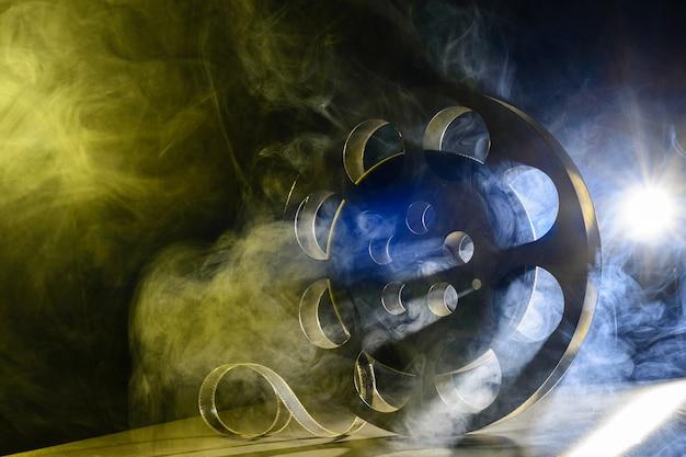 Kołowrotek do kina. martwa natura z akcesoriami do produkcji retro. koncepcja realizacji filmu. efekt koloru dymu na tle