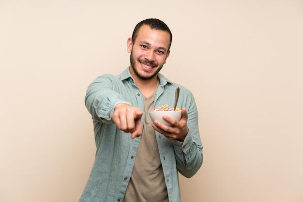 Kolumbijczyk z miską zbóż wskazuje na ciebie palcem
