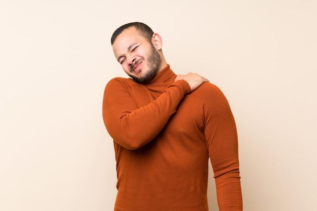 Kolumbijczyk z swetrem z golfem cierpiącym na ból w ramieniu za wysiłek