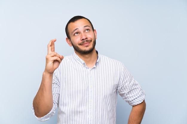 Kolumbijski mężczyzna nad odosobnioną błękit ścianą z palcami krzyżuje i życzy najlepszy